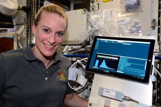 Astronaut Kate Rubins poses near a computer readout