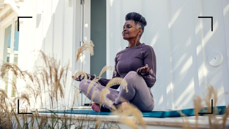 woman sitting upright on yoga mat outside