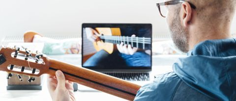 Orange Learn review: Image of man holding guitar watching laptop screen