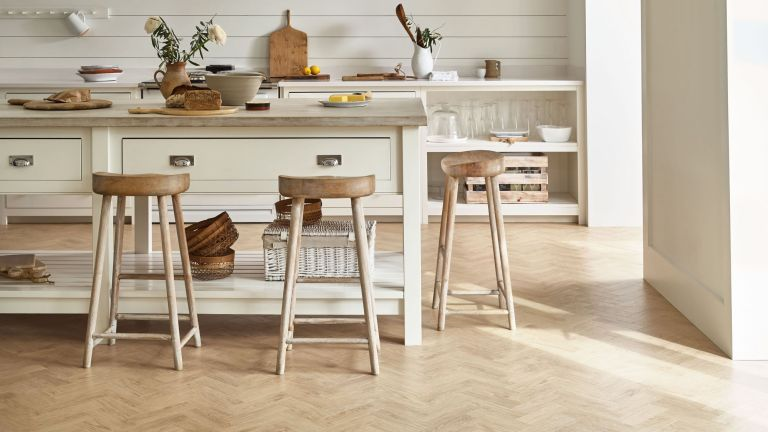 Pale oak wood-effect vinyl kitchen flooring ideas in a cream scheme with wooden stools.
