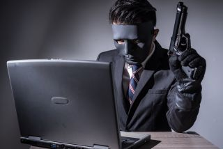 Abstract image of hacker or criminal wearing a mask and suit, using a laptop and holding a gun.