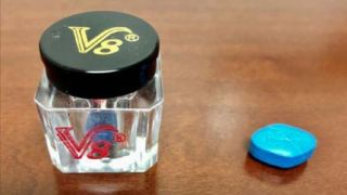 "A jar of ""V8"" male enhancement supplements, which contain blue tablets that closely resemble prescription Viagra."