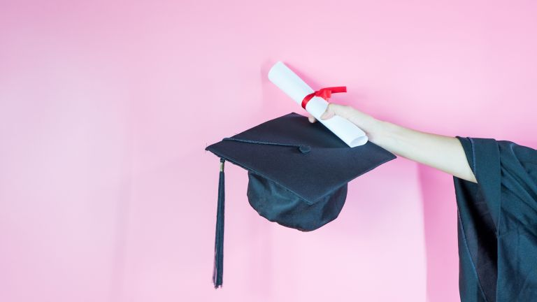 Paxton Smith, valedictorian abortion speech A hand holding graduation cap and diploma on pink background