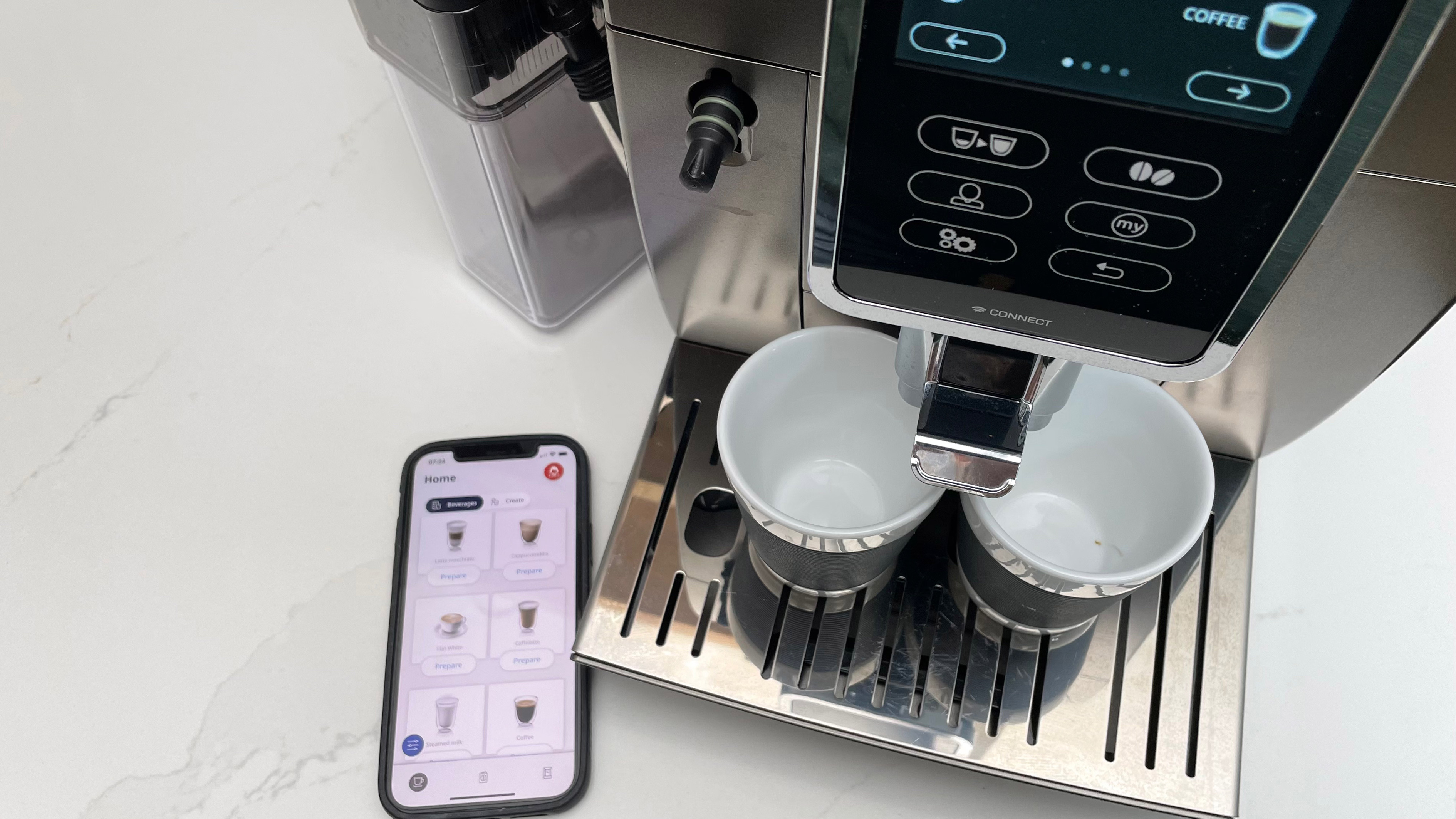 Looking down onto the De'Longhi Dinamica Plus as its ready to paur an espresso with the app onpen on a smartphone to the left-hand side