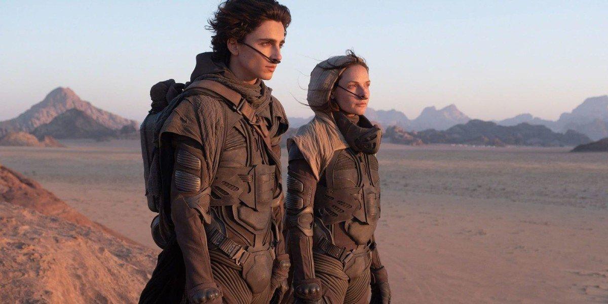 Dune Timothee Chalamet and Rebecca Ferguson wearing stillsuits in the desert
