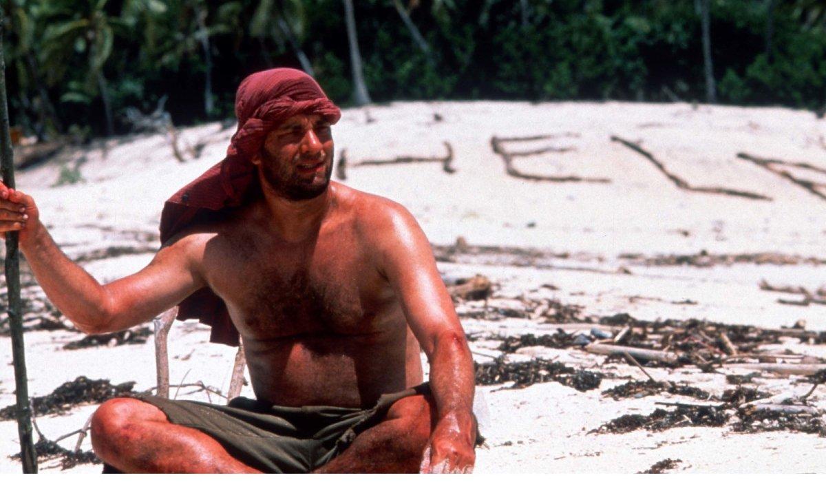 Cast Away Tom Hanks sits on a beach, with a stick