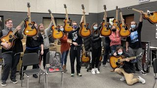 "Students from Upperman High School in Baxter, TN, holding their new guitars, the result of a grant from the Guitar Center Music Foundation, who drew from Guitar Center's in-store and online fundraising initiatives known as the ""Round Up Your Change"" program."
