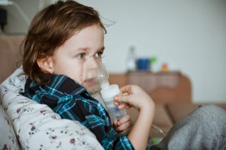 A preschool-age child using a nebulizer while relaxing on the couch.