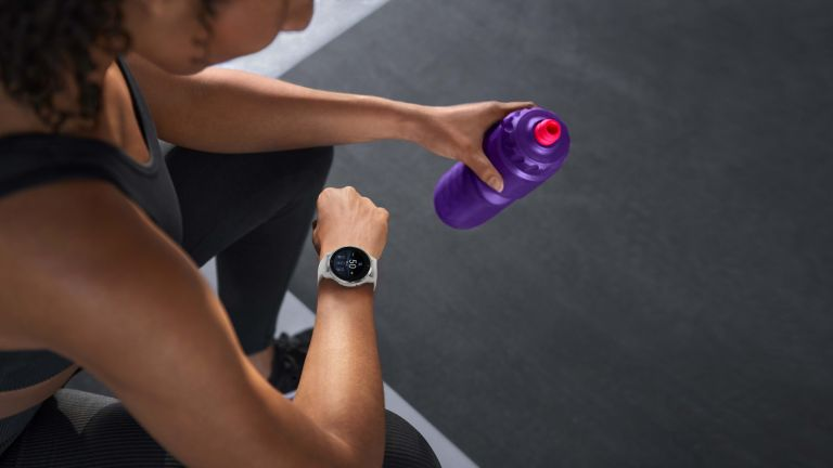person looking at their Garmin running watch checking their hydration reminder while holding a water bottle in their other hand