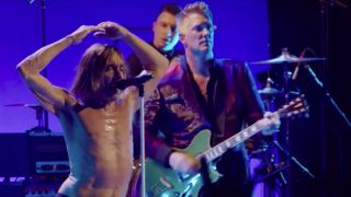 A picture of Iggy Pop on stage with Josh Homme and Matt Helders