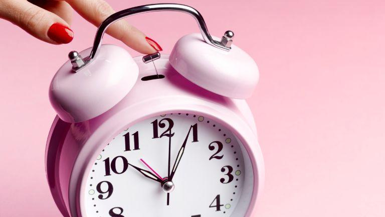 Pink alarm clock on pink background