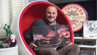 A photograph of Al Murray holding a Genesis record