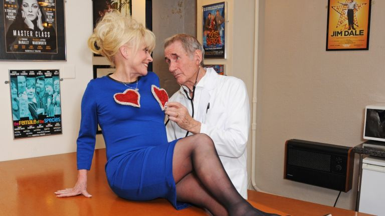 """Dame Barbara Windsor (L) and Jim Dale recreate a famous scene from their 1969 film """"Carry On Again Doctor"""" backstage following the press night performance of """"Just Jim Dale"""" at Vaudeville Theatre on May 28, 2015 in London, England"""