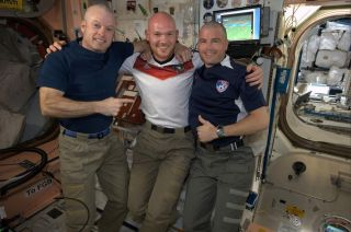 Three International Space Station crewmembers line up after two had their heads shaved