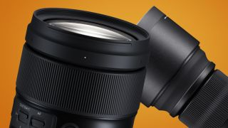 The Tamron 35-150mm f/2-2.8 in front of a Sigma lens on an orange background
