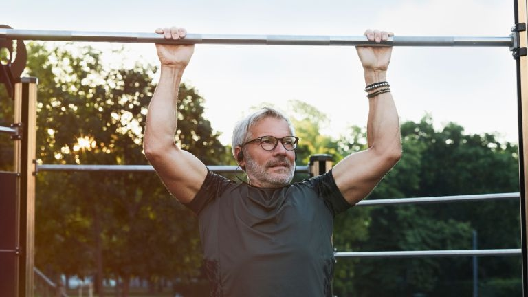Active 50 year old man doing pull-ups to increase his metabolism