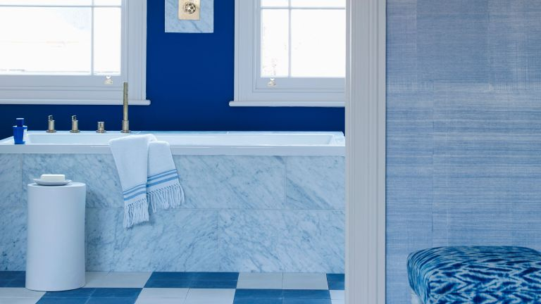 An example of blue bathroom ideas showing a blue ensuite with a checkered blue and white floor