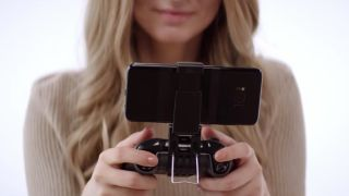 A woman holds an xbox wireless controller with a phone clip for mobile gaming