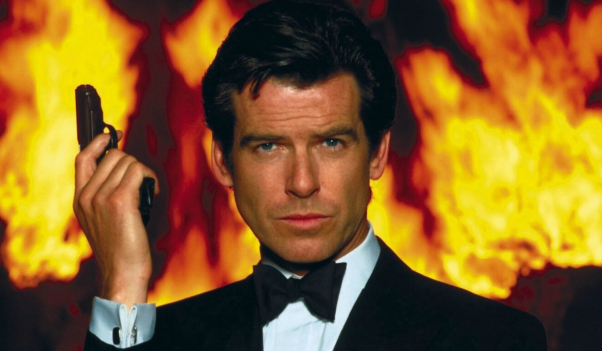 Goldeneye Pierce Brosnan stands in front of fire, with a gun in his hand