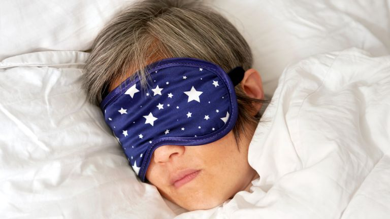 Mature woman sleeping in bed with eye mask close up