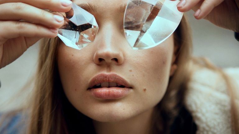 Face shot of woman covering eyes with glass crystals - stock photo