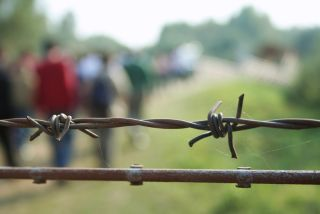 barbed wire with migrants in the background.