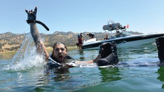 A photograph of Robb Flynn giving the devil horns in the water