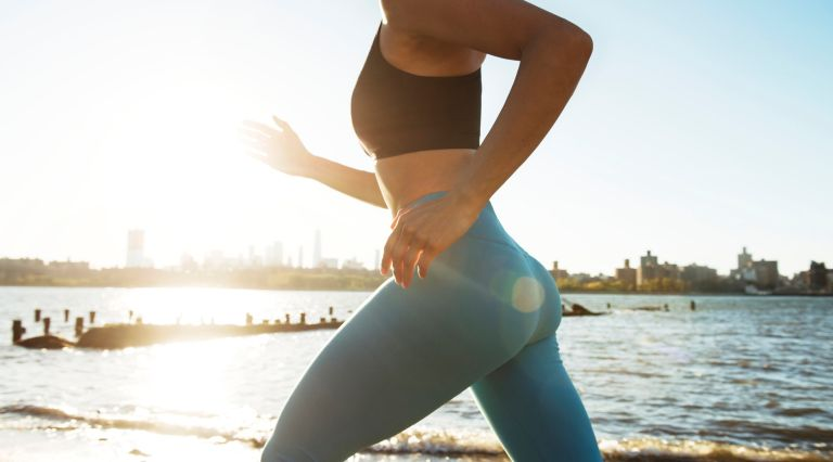 Midsection of young woman jogging in leggings by river against cityscape and clear sky during sunny day