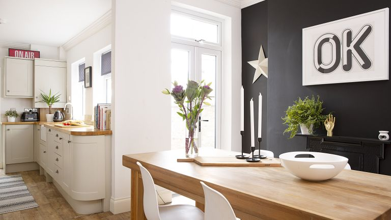 dining area with black feature wall and a shaker style kitchen