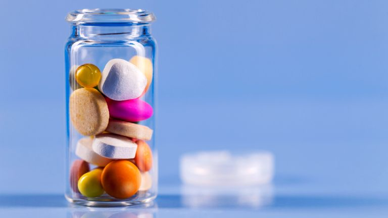 Glass jar filled with immunity supplements on a blue background