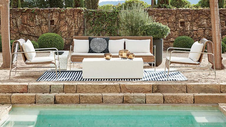 A black and white striped outdoor rug with a contemporary rattan lounge set byt the side of a swimming pool