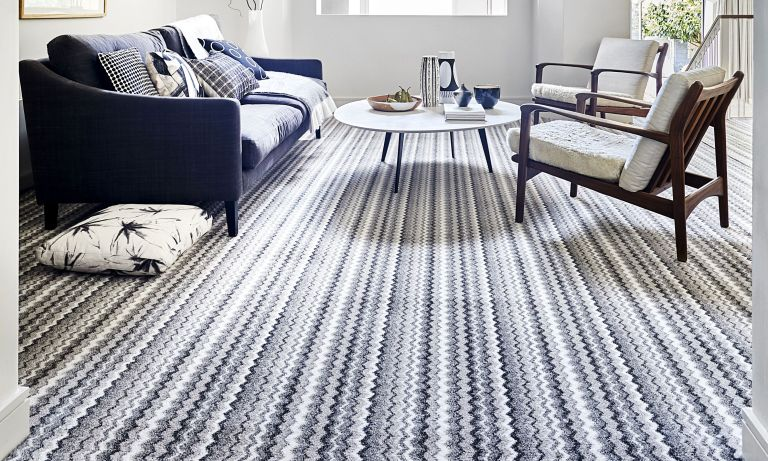 Striped white and navy carpet in lounge with wooden seating and glass topped coffee tabel