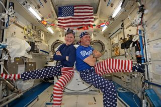Two astronauts pose back to back in an ensemble of red, white and blue clothing