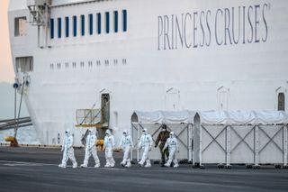 Спешните работници излизат от круизния кораб Diamond Princess, където хиляди остават под карантина.