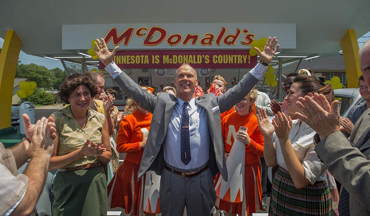 The Founder Michael Keaton raises his hands in celebration at a McDonalds