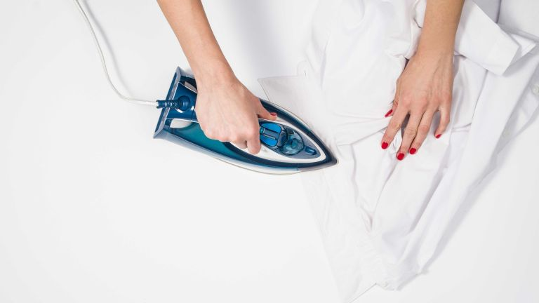 Best steam iron: woman ironing shirt