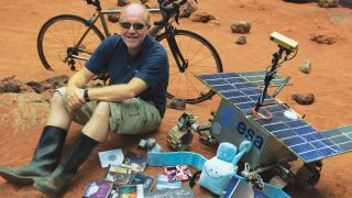 Mark McCaughrean sitting on an orange hill surrounded by records and space agency items