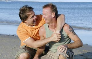 A gay couple laughing on the beach.