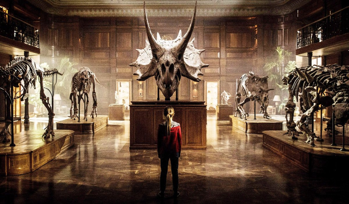 Jurassic World: Fallen Kingdom Maisie stands in front of a Triceratops skull