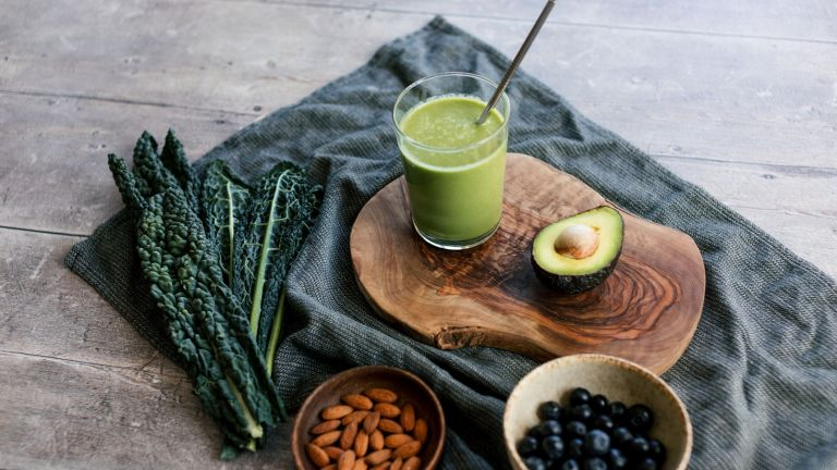 a green smoothie and smoothie ingredients on a tablecloth, on a table