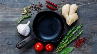 A cast iron skillet surrounded by ginger, garlic and rosemary