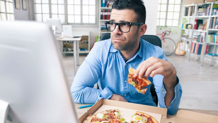 Unhappy man eating pizza at his computer, illustrating that diet changes can make all the difference when it comes to how we look and feel