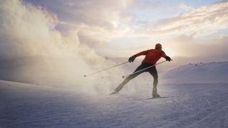 A man skate skiing at sunset