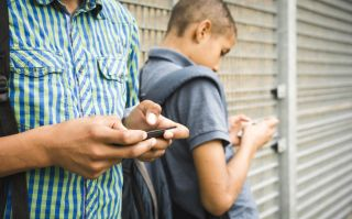 Two teenage boys leaning against a wall texting on smartphones. best encrypted messaging apps