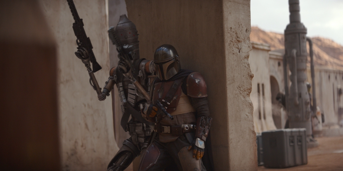 IG-11 and The Mandalorian take cover behind a wall.