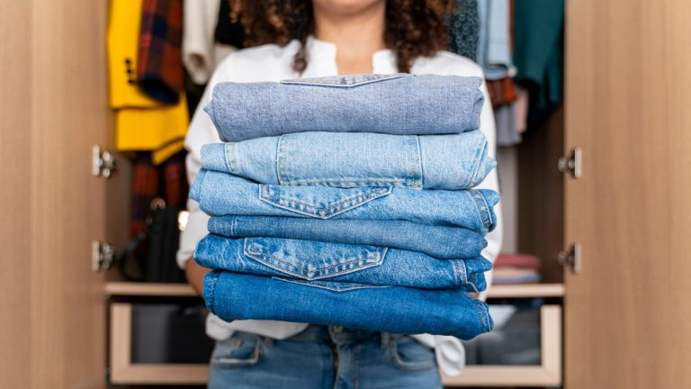 longest lasting jeans: woman holding a pile of jeans