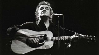 A photograph of Johnny Cash playing live