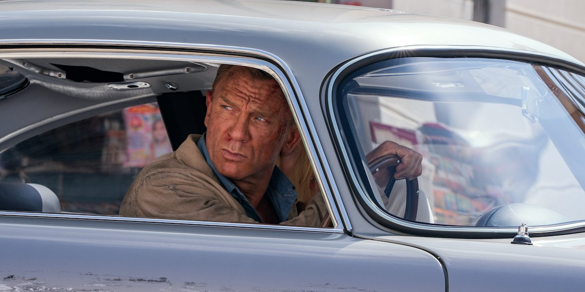 A bloodied James Bond drives a car in 'No Time To Die'