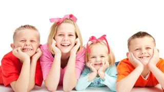 Four boys and girls lie on floor smiling broadly into camera.
