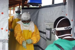 Staff members of Médecins Sans Frontières, or Doctors Without Borders, conduct a decontamination process on Dr. Tom Frieden, CDC Director, who is dressed in his personal protective equipment and is exiting an Ebola treatment unit in Monrovia, Liberia.